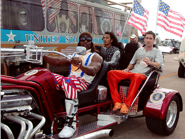 IDIOCRACY (2006) Luke Wilson (R) and driving Terry Crews